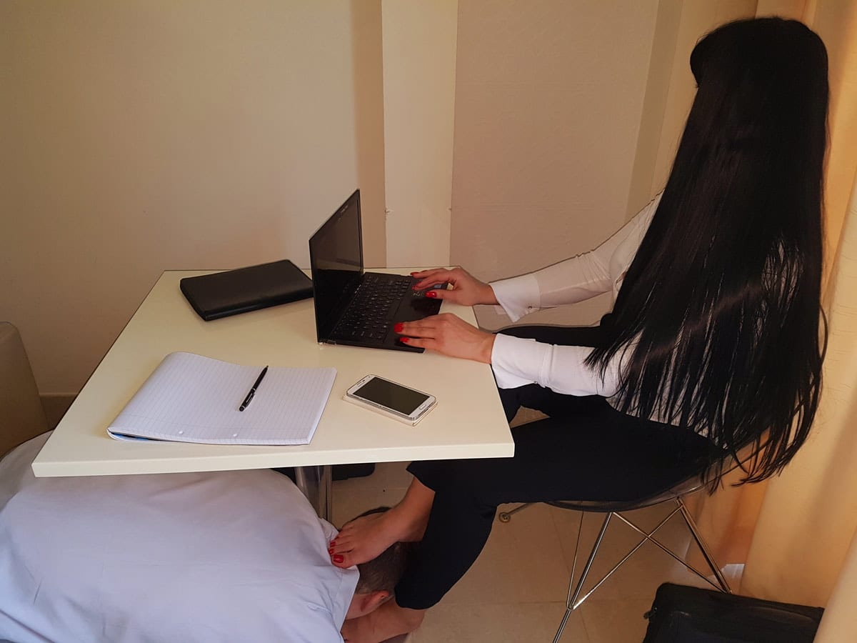 An office role play showing Mistress Anita as the C.E.O. sitting at her desk working on her Sony laptop while her sub as the badly performing employee is forced to be a foot slave to keep his job.