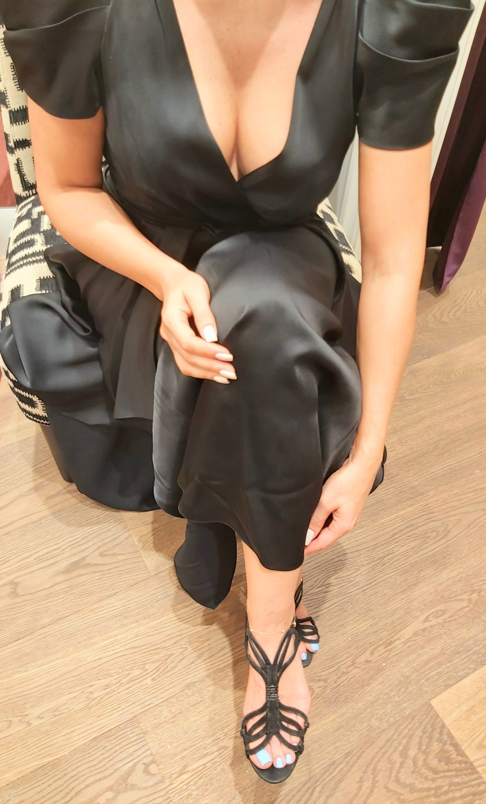 Dominatrix Anita is sitting on a fauteuil with black and white upholstery wearing a black satin dress with black open sandals and blue polished toe nails are showing.