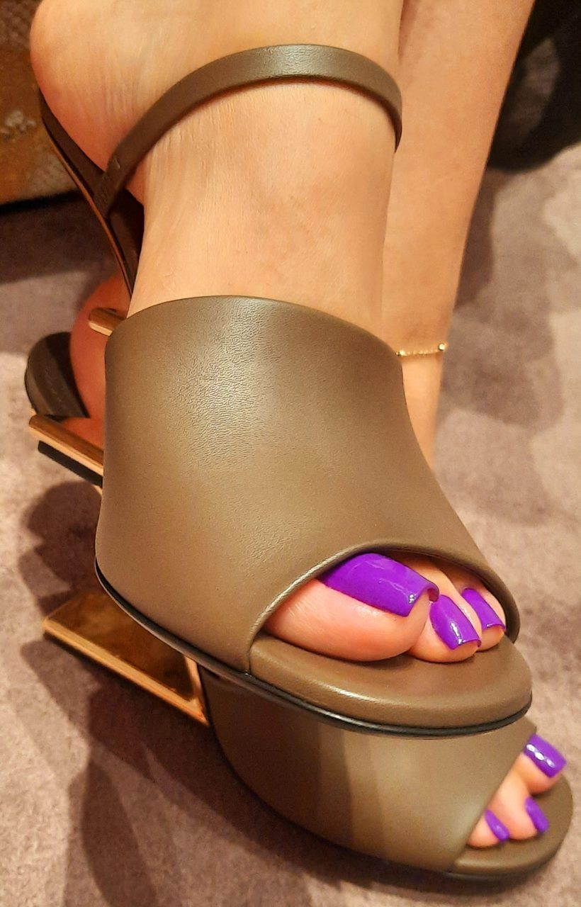 Mistress Anita's toes with purple nail polish are showing in brown calf leather high-heeled Fendi sandals with a sculpted gold-coloured metal heel.