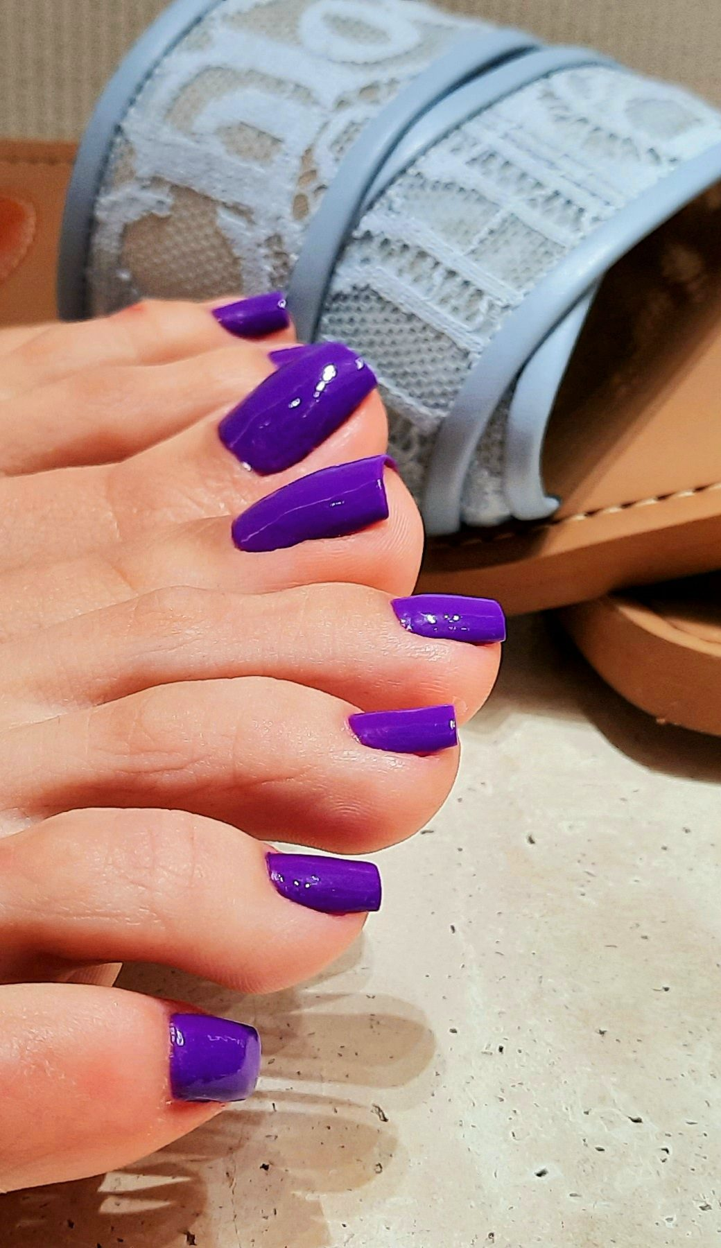 Toes of two feet with purple nail polish and in background baby blue Chloe flat sandals