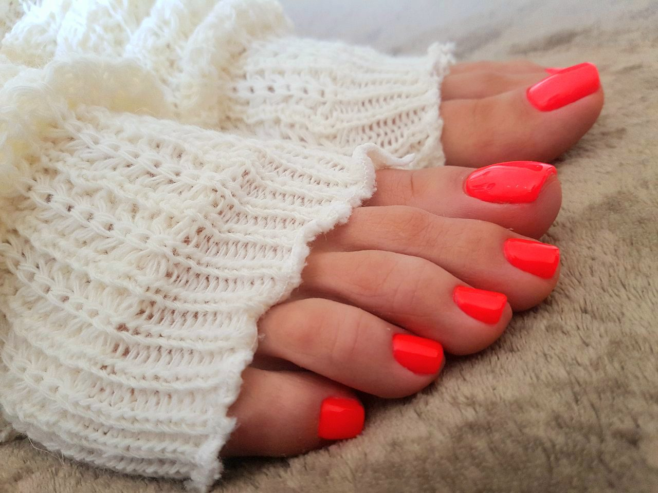 Feet resting on a brown blanket, most of feet covered with woolen white leg warmers and only toes with red polish visible.