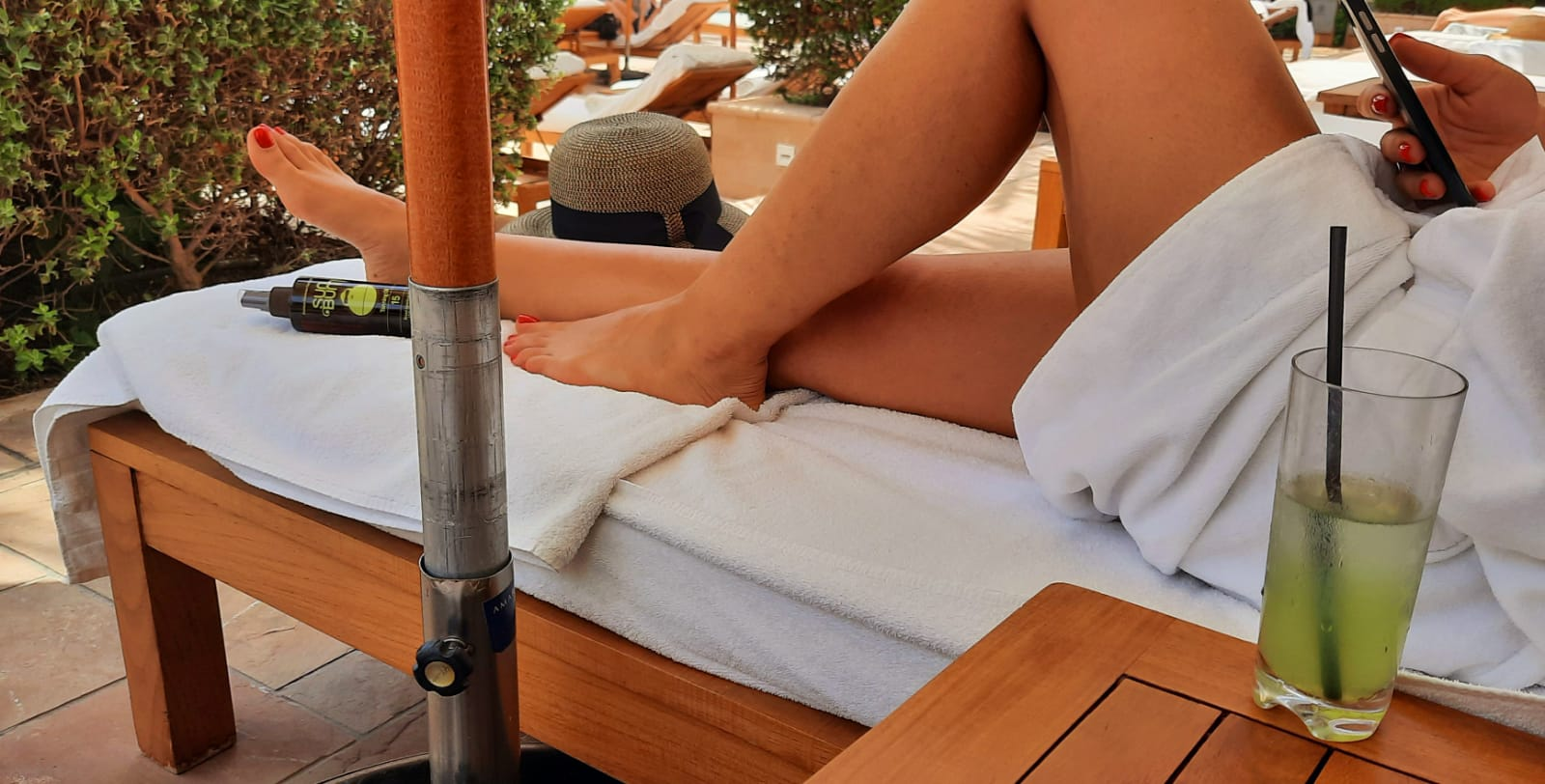 Mistress Anita is lying on a wooden sunbed which is covered with white towels, a hat and tanning oil, she is holding a smart phone and is wearing a white bathrobe showing her legs and feet with red polish, on the left of her is a wooden table with a glass with a green beverage with a black straw.