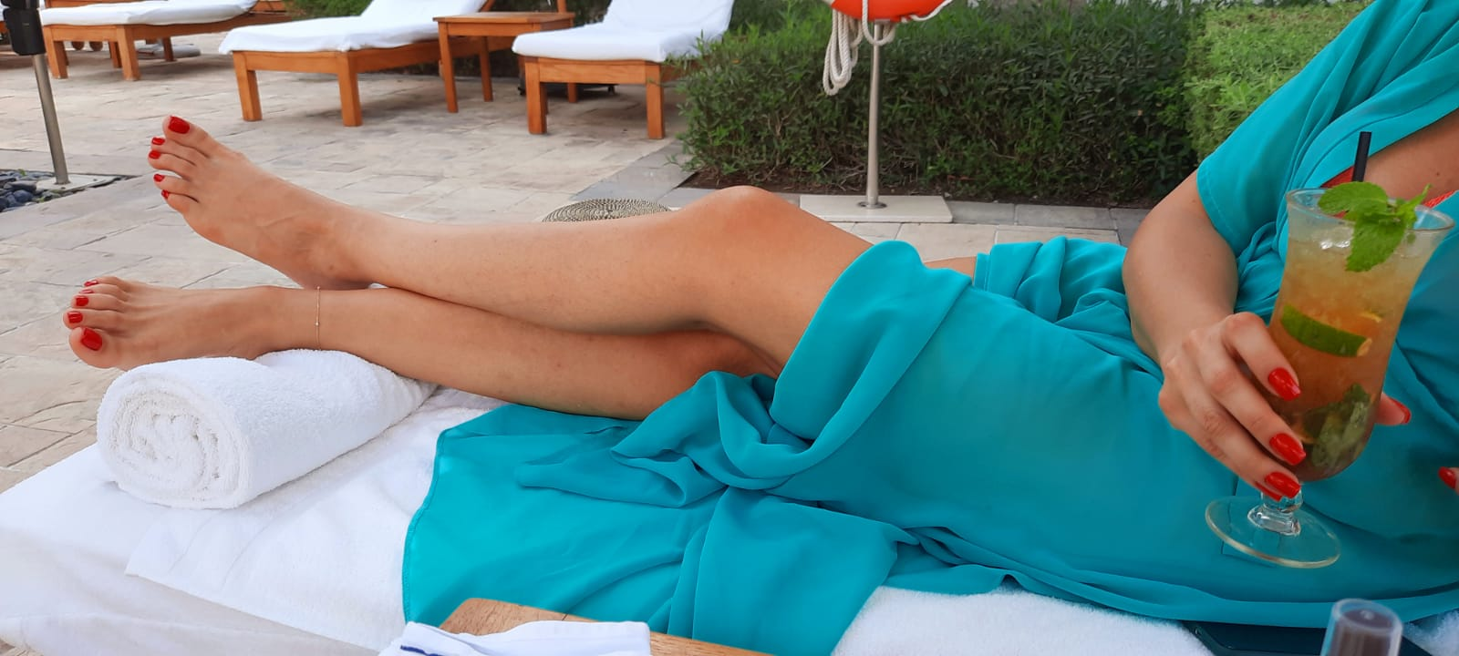 Goddess Anita is in a garden lying on a sun bed which is covered with white towels and she is wearing a turquoise beach dress, her legs are visible and her feet have red pedicured toe nails and in her right hand she is holding a tall cocktail with a straw and mint garnish.